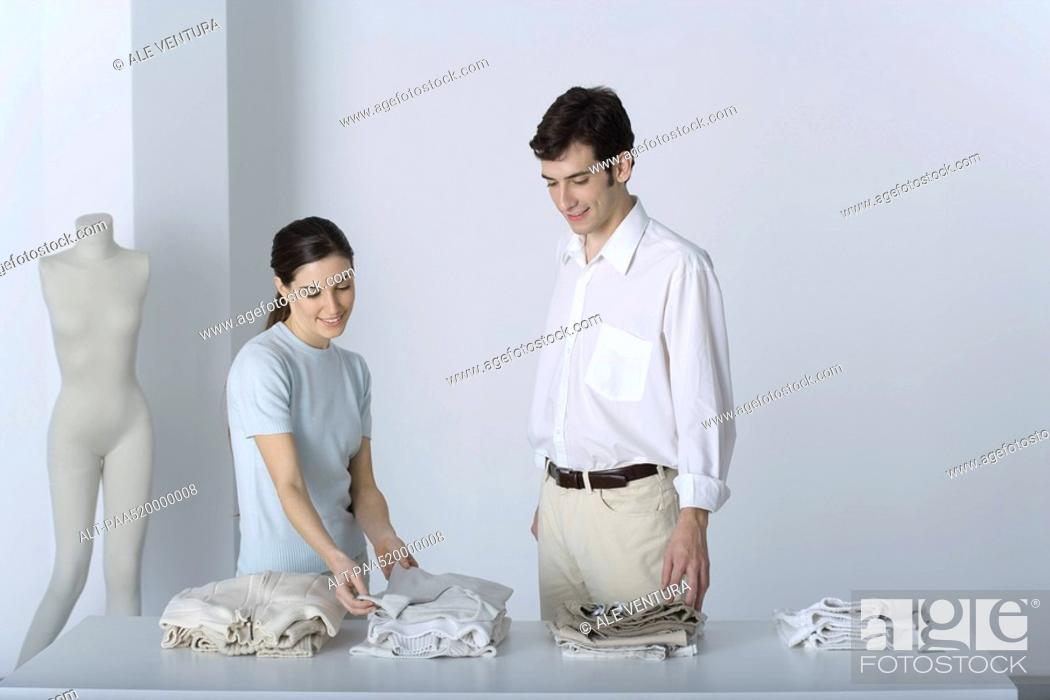 Stock Photo: Saleswoman showing male customer a sweater, both smiling.