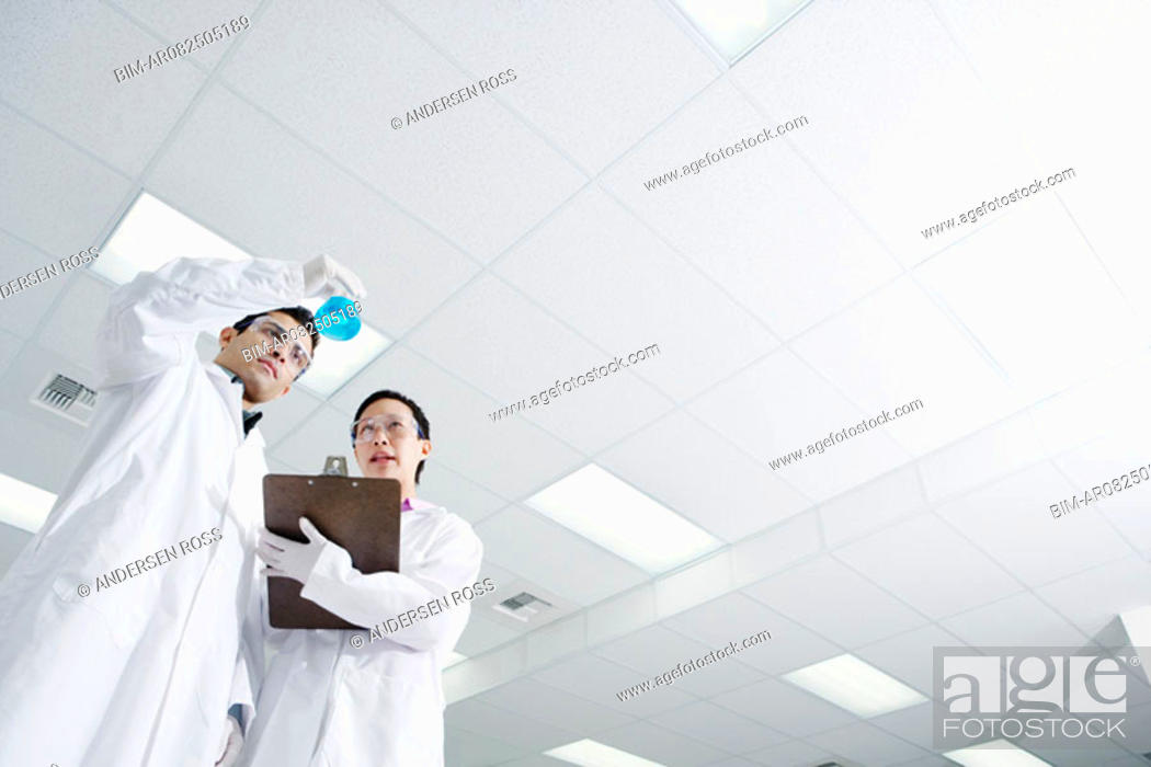 Stock Photo: Low angle view of two technicians looking at vial of liquid.