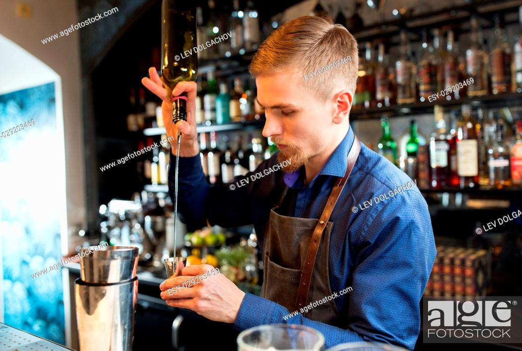 Stock Photo: drinks, people and luxury concept - barman with shaker pouring alcohol from bottle into jigger and preparing cocktail at bar.