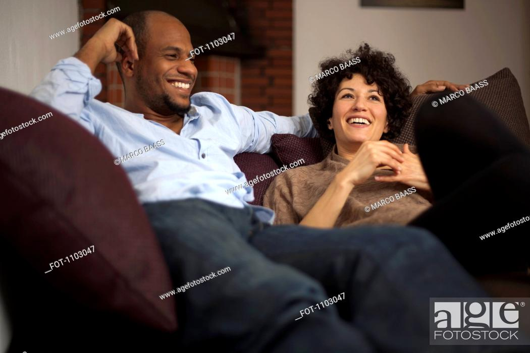 Stock Photo: A laughing couple relaxing together on a sofa.