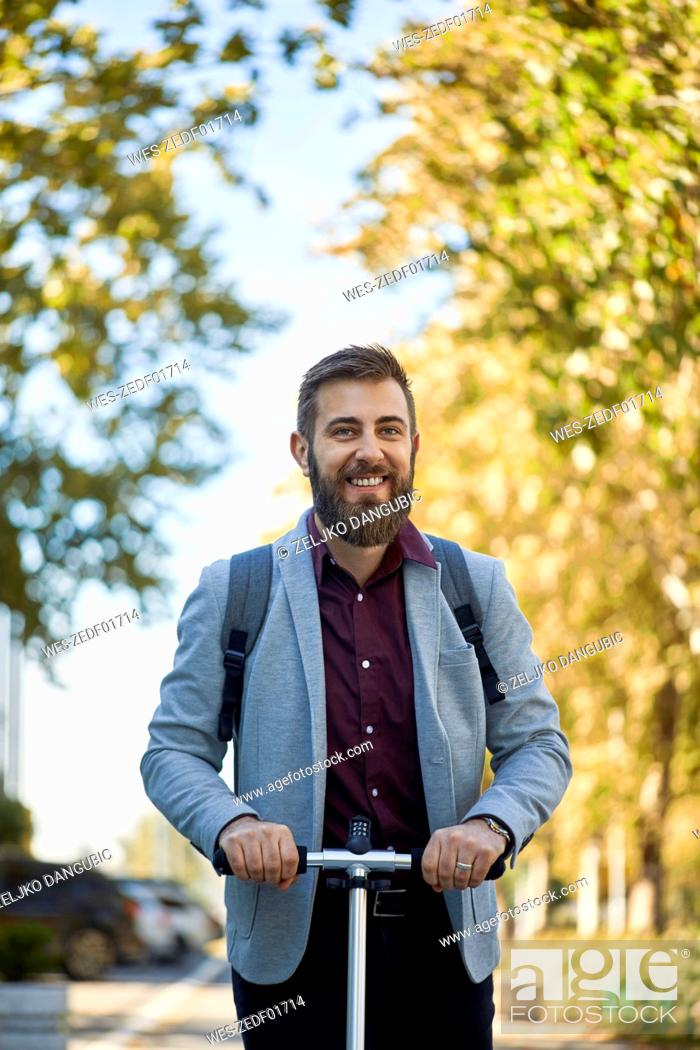 Stock Photo: Portrait of smiling businessman with scooter.