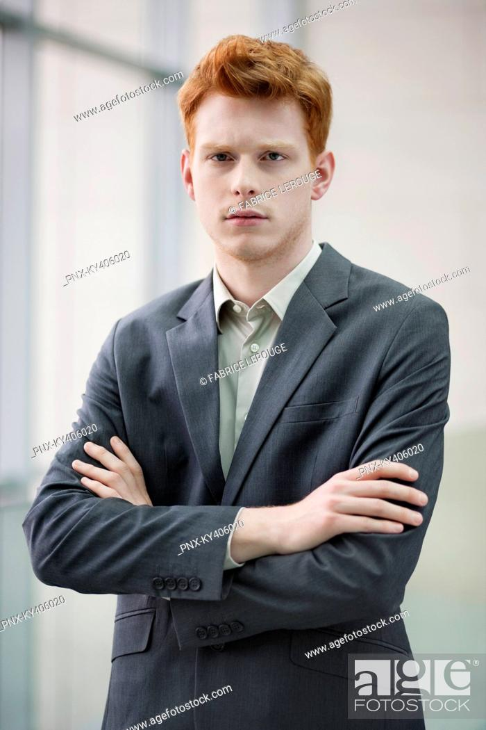 Stock Photo: Portrait of a businessman with arms crossed in an office.