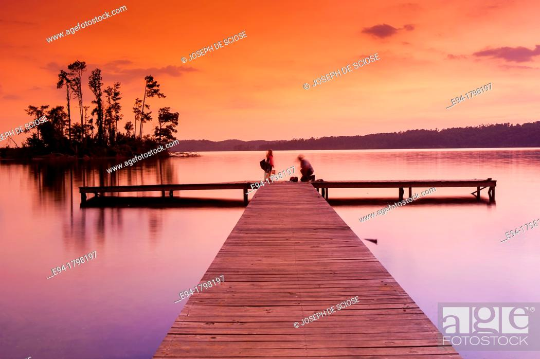 Stock Photo: Sunset over a lake with a small boat dock and fishermen silhouetted in the foreground, Lake Guntersville State Park, Alabama, USA.