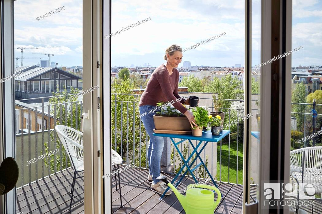 Imagen: Smiling mature woman caring for plants on balcony.