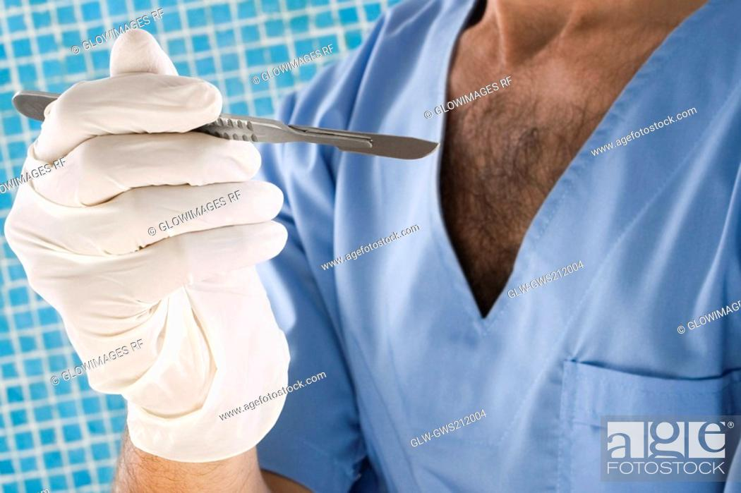 Stock Photo: Mid section view of a male surgeon holding a scalpel.