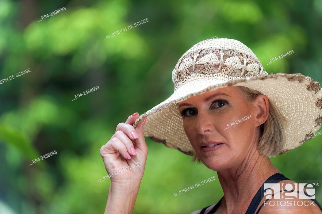 Stock Photo: A portrait of a 56 year old blond woman wearing a straw hat and looking directly at the camera, outdoors.