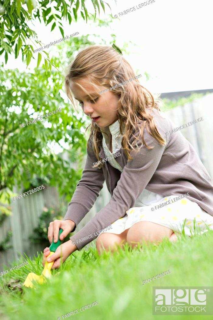 Stock Photo: Girl gardening with a trowel.