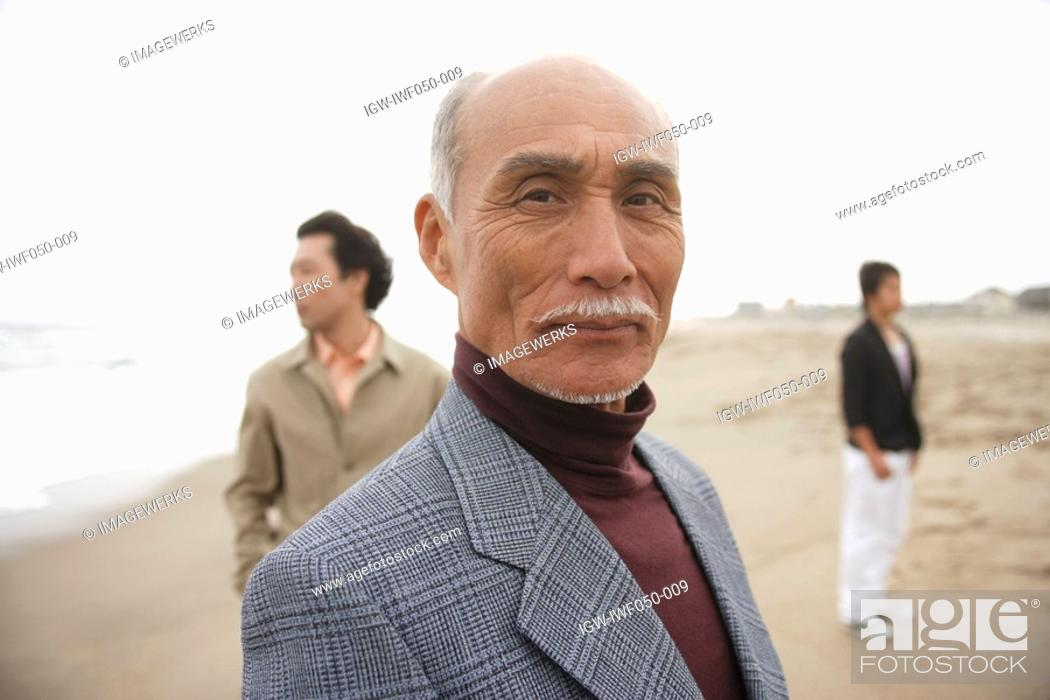 Stock Photo: Senior man smiling while son and grandson standing in background.
