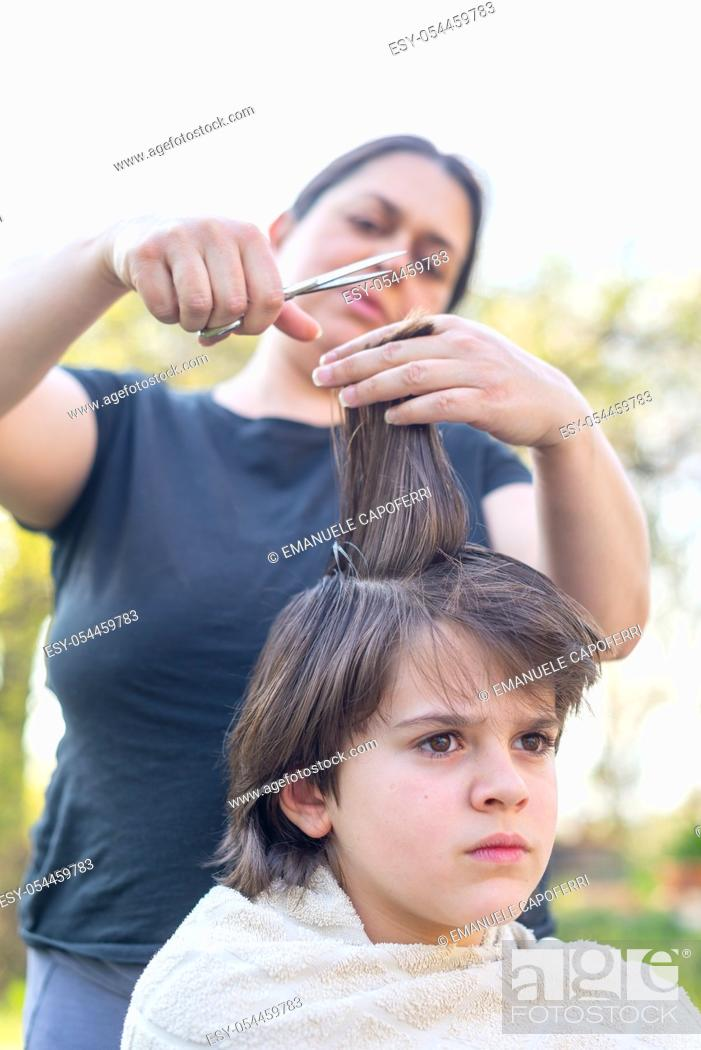 Stock Photo: mother cuts her son's hair in the garden - at home the mother is a hairdresser for her son.