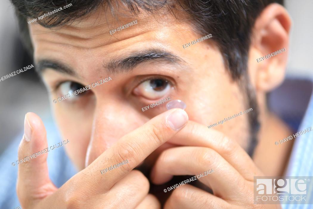 Stock Photo: Man putting on contact lens in ophthalmology clinic .