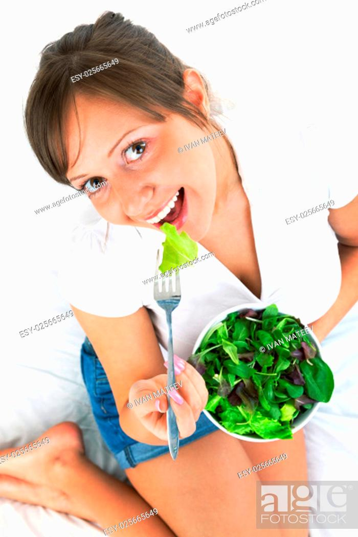 Stock Photo: Young woman eating fresh salad isolated on white background.
