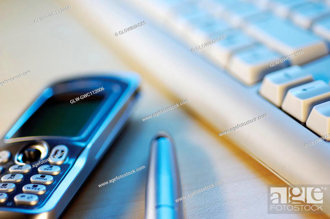 Stock Photo: Close-up of a mobile phone with a pen and a computer keyboard.
