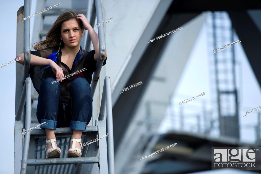 Stock Photo: Young, fashionable woman from Afghanistan, living in asylum in the Netherlands, posing near the docks of Rotterdam harbor.
