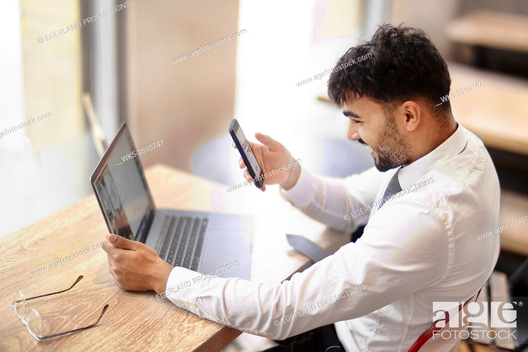 Stock Photo: Businessman comparing differing appearance of internet website on laptop and on smartphone.