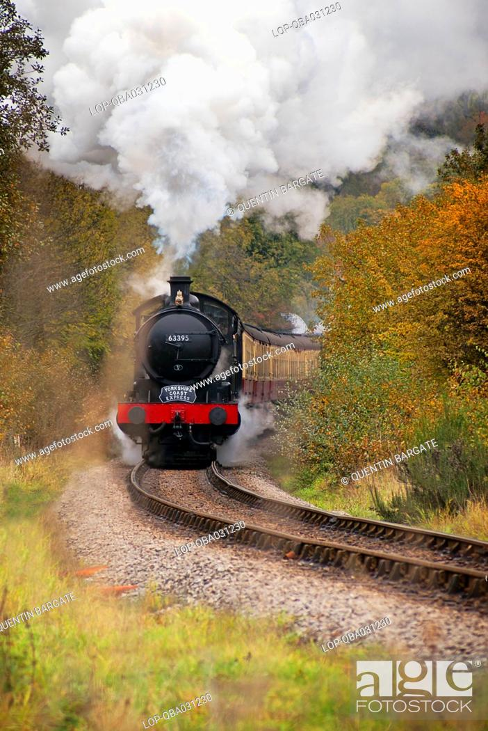 Stock Photo: England, North Yorkshire, Grosmont. The Yorkshire Coast steam express on the North Yorkshire Moors Railway NYMR travelling through the Esk Valley.