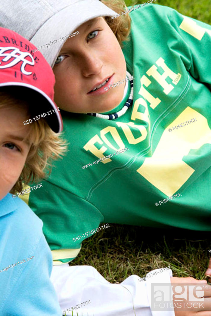 Stock Photo: Portrait of two boys reclining on grass.