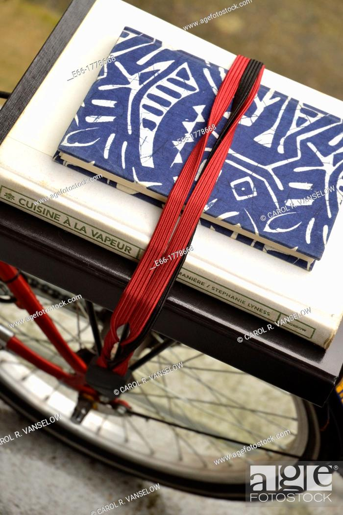 Stock Photo: books on rear bike rack of fold-up bicycle.