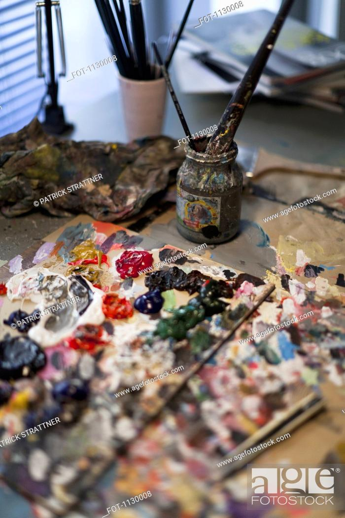 Stock Photo: Oil paint on a palette and paintbrushes in a jar.
