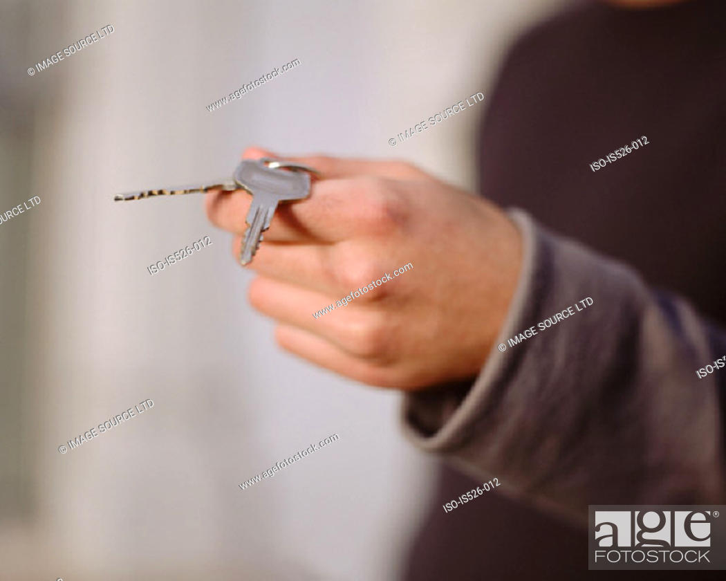 Stock Photo: Young man holding keys.