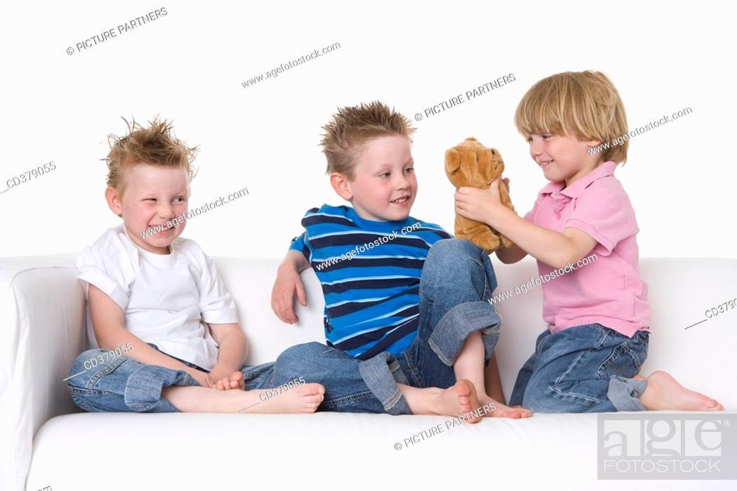 Stock Photo: Three boys sitting on a bench.
