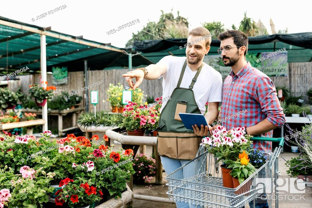 Imagen: Worker with tablet in a garden center advising customer.