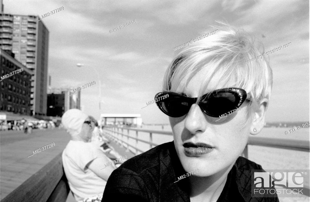 Stock Photo: Chic woman in sunglasses sits on bench in New York's Coney Island boardwalk. Model-Released Image. Release Number 1001.