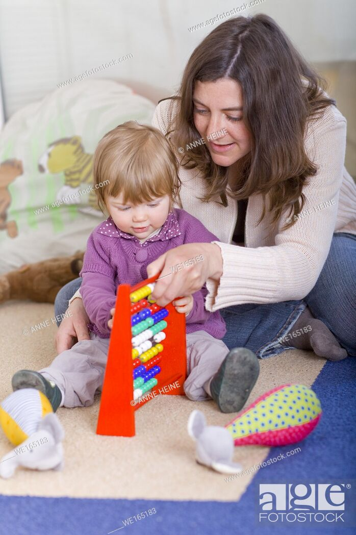 Stock Photo: girl one year old with mom and slide rule.