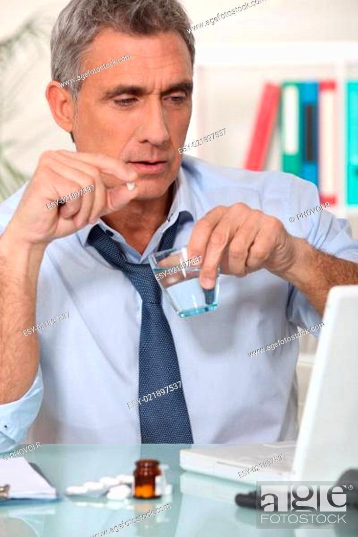 Stock Photo: Businessman taking his medication.