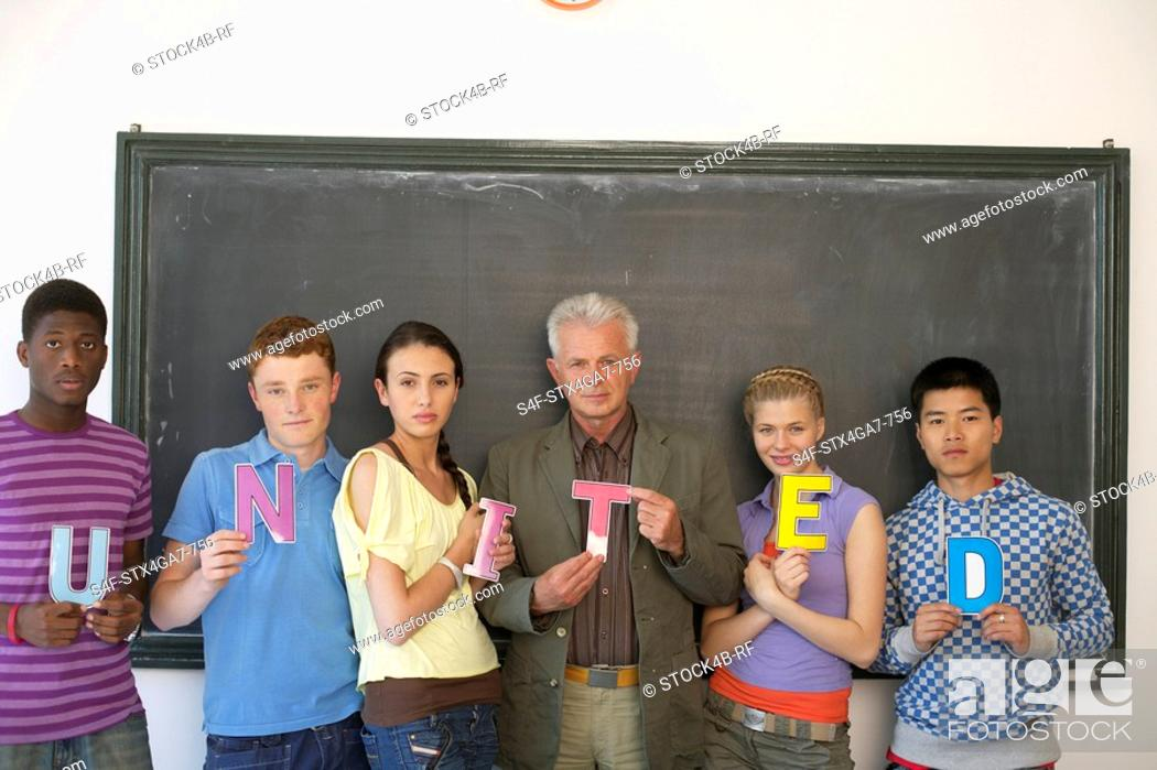 Stock Photo: Students and professor in front of a blackboard holding letters.
