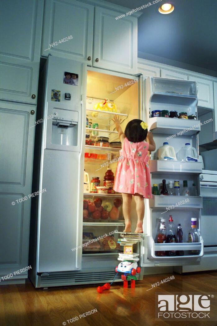 Stock Photo: Girl standing on stuff reaching for cake.