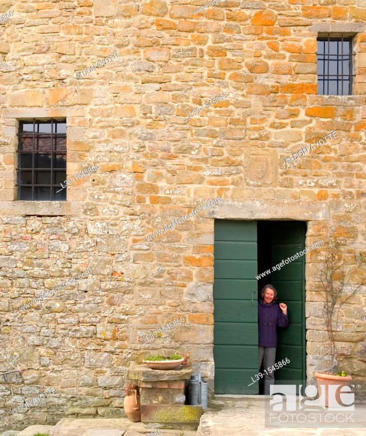Stock Photo: Woman waving from a doorway in Tuscany, Italy.