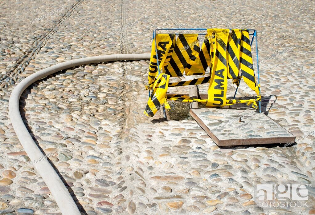 Stock Photo: Hose pumping water from a fire hydrant embedded in a cobble stone street, marked with cordon tape for safety reasons. Cordoba, Spain.
