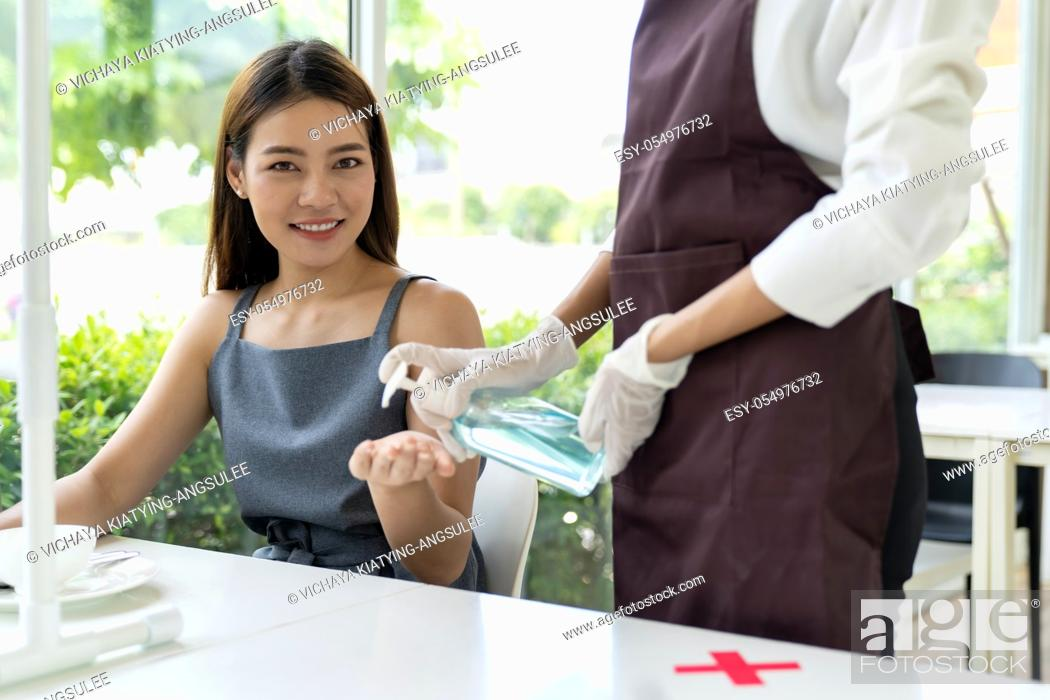 Stock Photo: Waitress push alcohol gel hand sanitizer for customer at dining table for hygiene hand cleaning reduce infection and spreading coronavirus covid-19 pandemic.