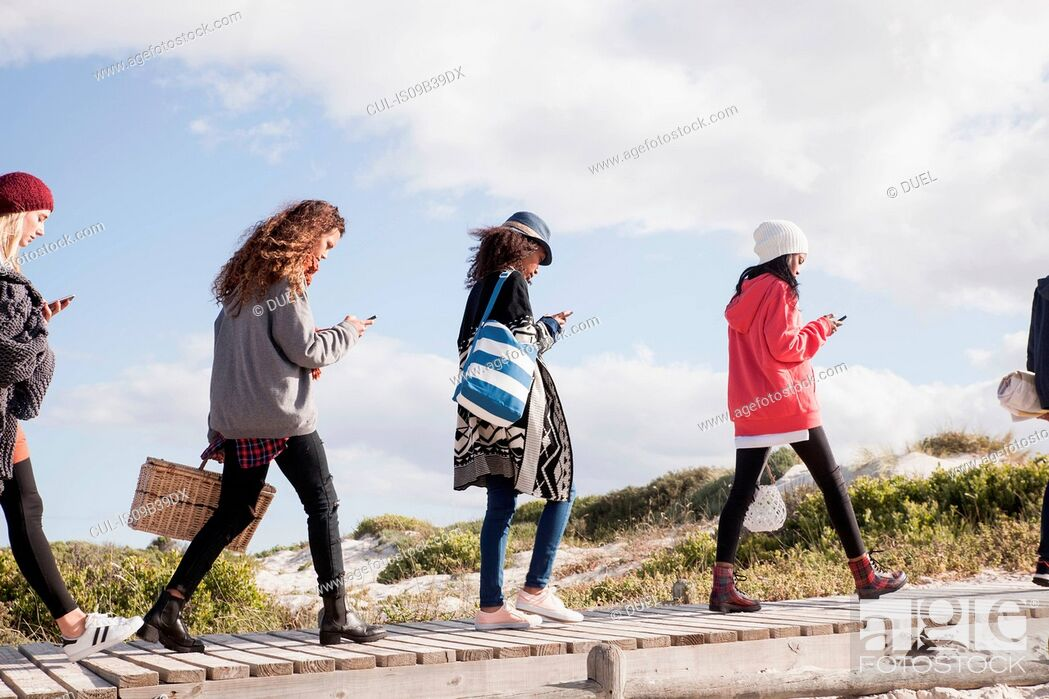 Stock Photo: Row of young adult friends strolling along beach boardwalk reading smartphones, Western Cape, South Africa.