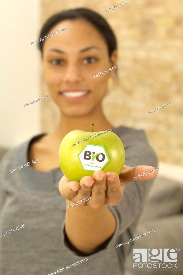 Stock Photo: Woman holding organic apple.