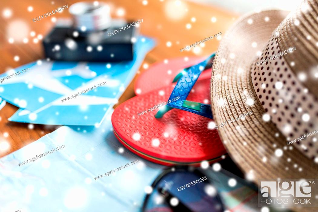 Stock Photo: vacation, tourism and objects concept - close up of travel map, airplane tickets, flip-flops and hat.