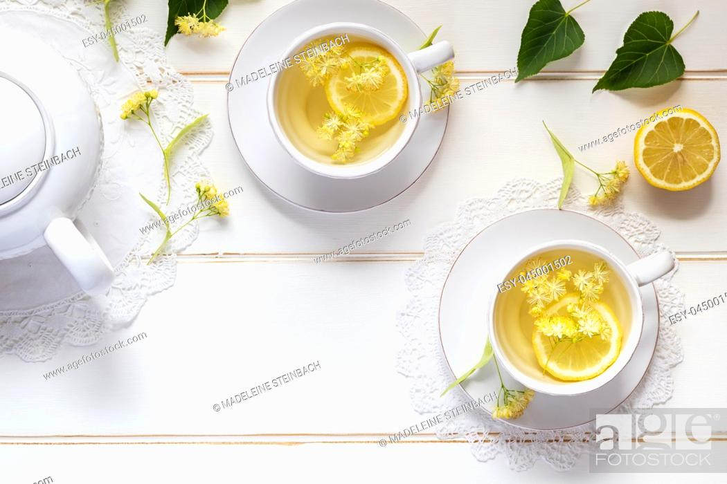 Stock Photo: Two cups of herbal tea with linden flowers and lemon on a white table, with copy space.