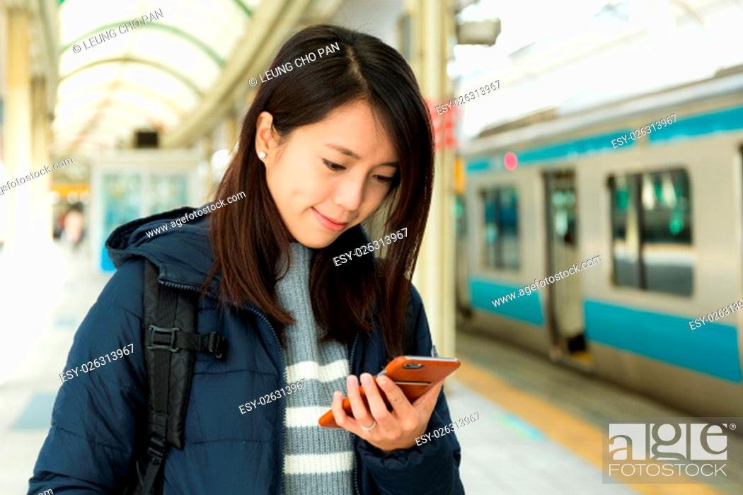 Stock Photo: Woman reading message on cellphone in train station.