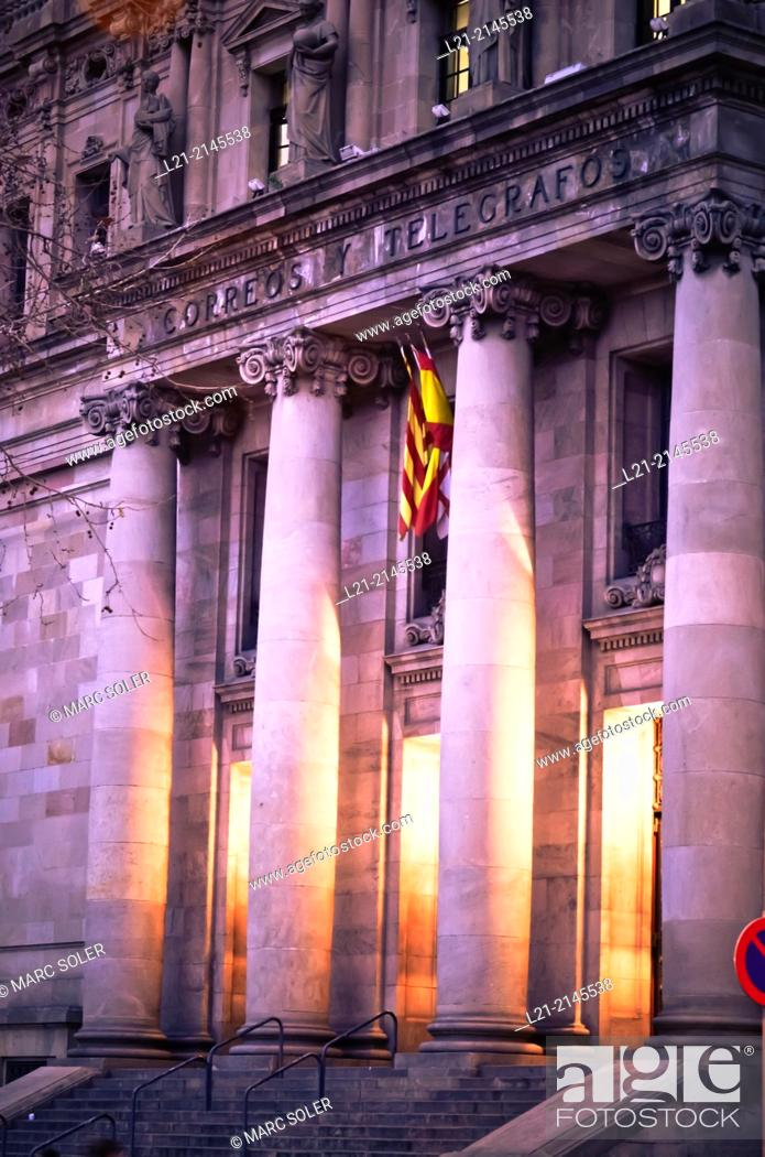 Stock Photo: Columns and interior light at dusk, night. View of central post office building designed by Josep Goday Casals and Jaume Torres Grau.