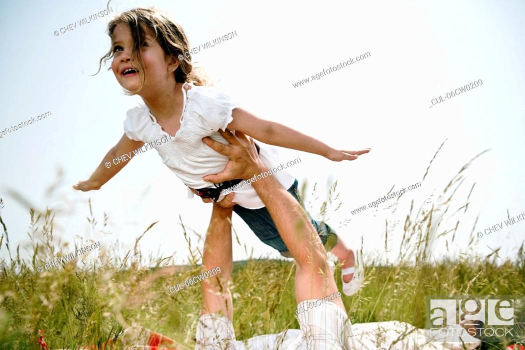 Stock Photo: Girl held aloft flying.