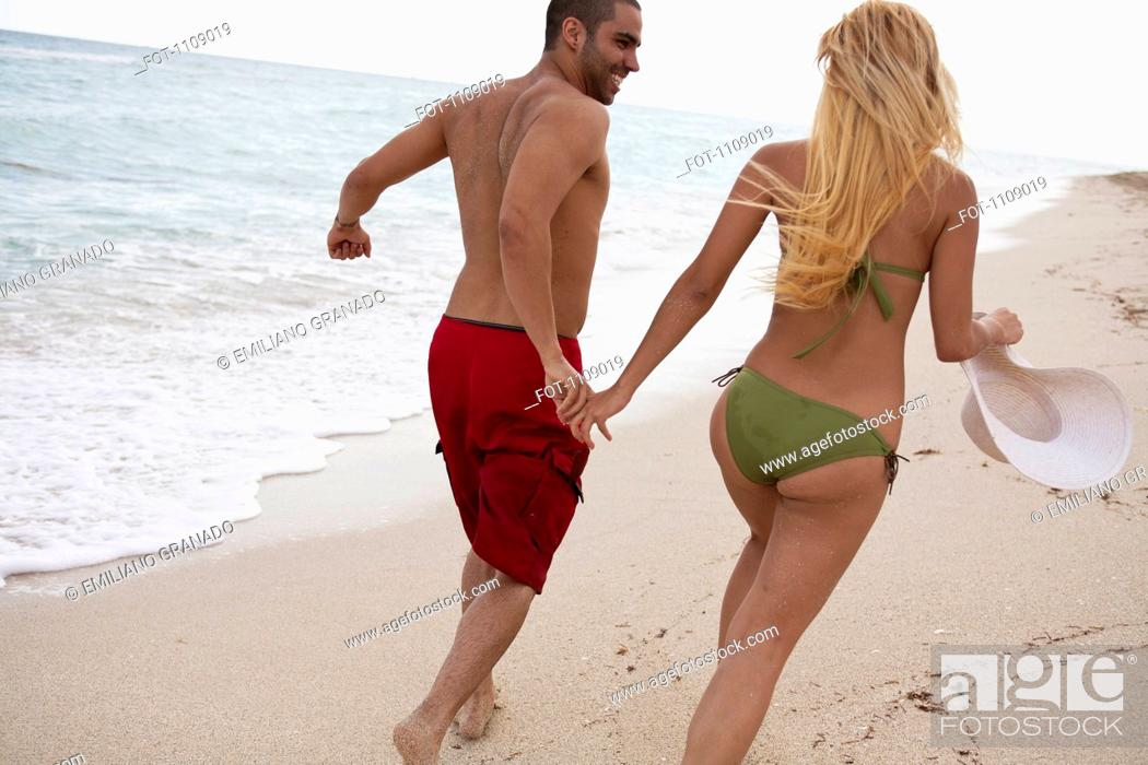Stock Photo: A young couple holding hands and running on the beach.