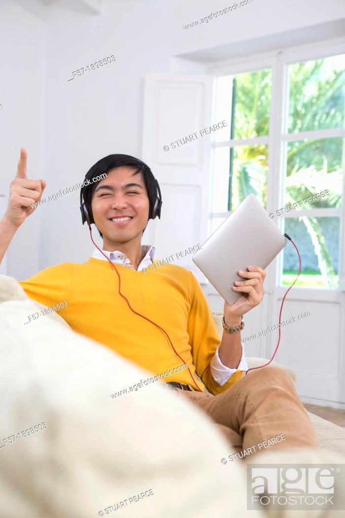 Imagen: Young Asian man using his Tablet computer.