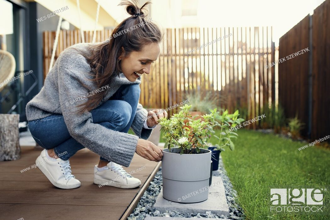 Imagen: Smiling young woman looking at potted plant in garden.
