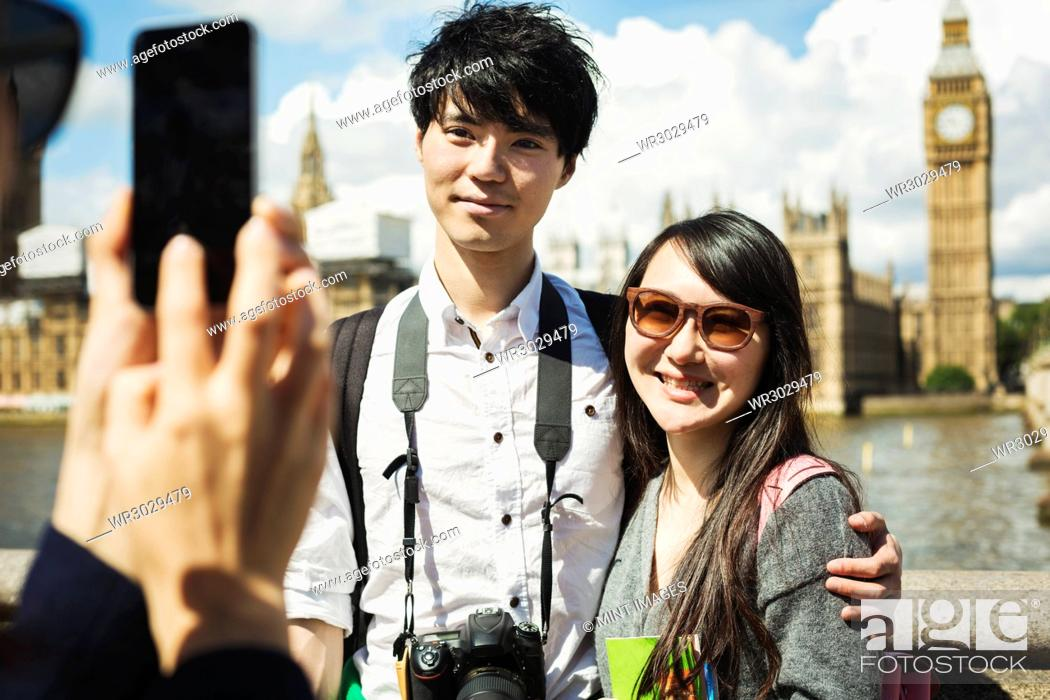 Imagen: Smiling woman with black hair taking picture of couple with smartphone, standing on Westminster Bridge over the River Thames, London.