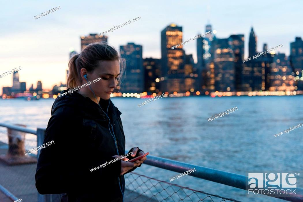 Stock Photo: Young woman by waterfront, using smartphone, Brooklyn, New York, USA.