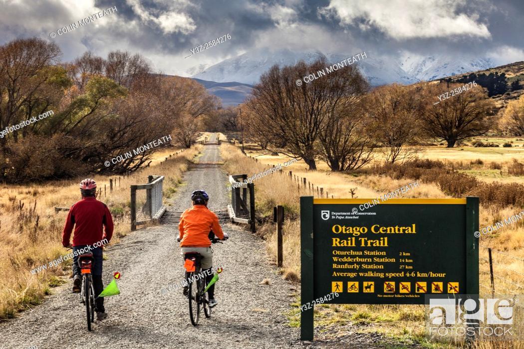 Stock Photo: Cyclists on Otago Rail Trail near Oturehua, gathering snow storm, Central Otago, New Zealand.