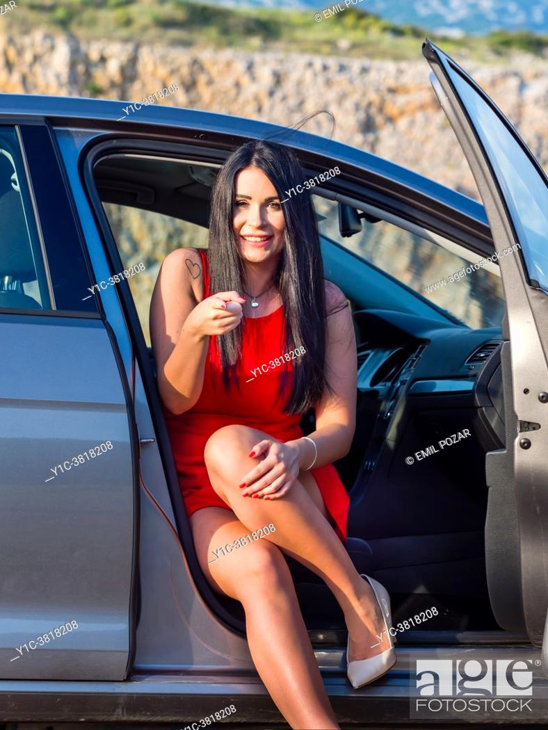 Stock Photo: Attractive young woman in a car in countryside in late afternoon pointing at camera.