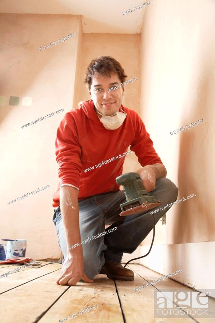 Stock Photo: Man holding sanding tool in unrenovated room portrait.