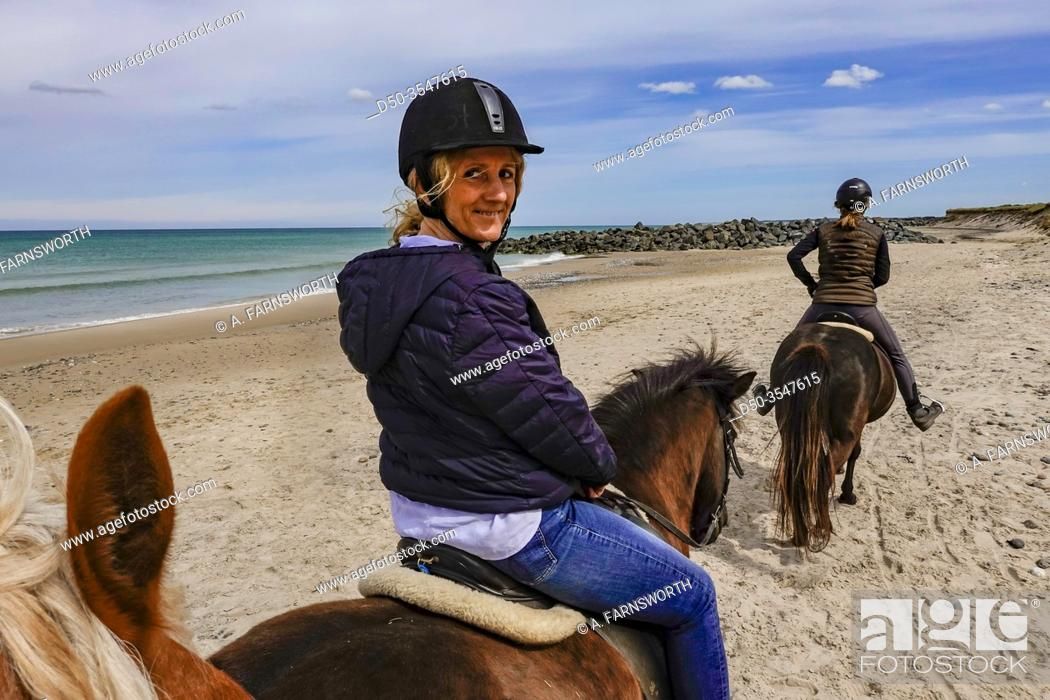 Stock Photo: Hirtshals, Denmark A middle-aged woman goes horseback riding on the beach.