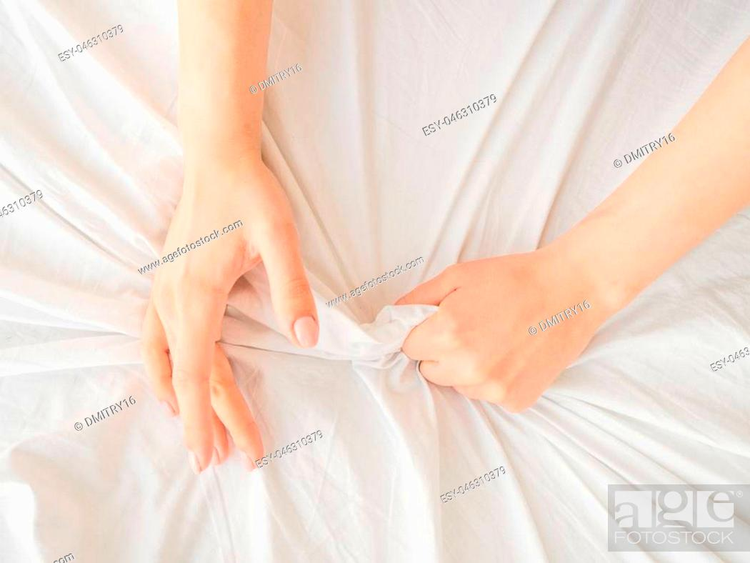 Stock Photo: Hand clutches or grasps a white crumpled bed sheet in a hotel room, a sign of ecstasy, feeling of pleasure or orgasm. Orgasm is the greatest point of sexual.